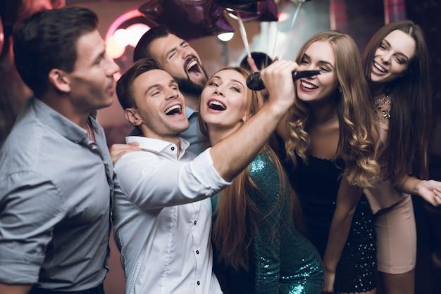 Młodzi ludzie w klubie tańczą i śpiewają