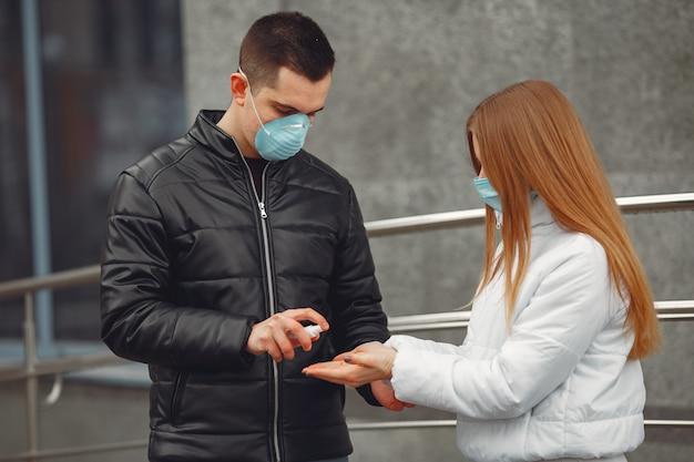 Młodzi ludzie w maskach ochronnych rozpylają środki dezynfekujące do rąk
