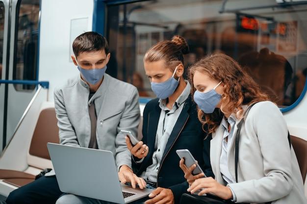Młodzi ludzie w maskach ochronnych siedzący w wagonie metra
