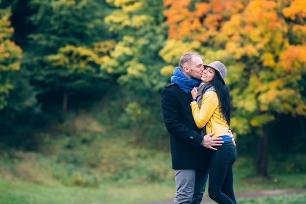 Młodzi ludzie w parku jesień. żółte drzewa i liście. szczęśliwa młoda koncepcja rodziny.