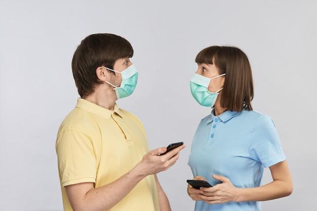 Młodzi ludzie w sterylnych maskach zaskakująco patrzą na siebie po obejrzeniu wiadomości w swoich telefonach, wiadomości o koronawirusie