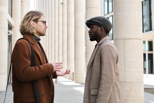 Młodzi ludzie w stylowych płaszczach rozmawiają ze sobą podczas spotkania na mieście
