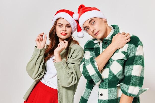 Młodzi ludzie w świątecznych kapeluszach na jasnym tle boże narodzenie nowy rok. wysokiej jakości zdjęcie
