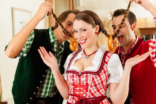 Młodzi ludzie w tradycyjnym bawarskim trachcie w restauracji lub pubie