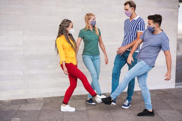 Młodzi ludzie witają się, aby uniknąć rozprzestrzeniania się koronawirusa - przyjaciele spotykają się zamiast powitania uściskiem lub uściskiem dłoni dotykają razem stóp - pojęcie dystansu społecznego