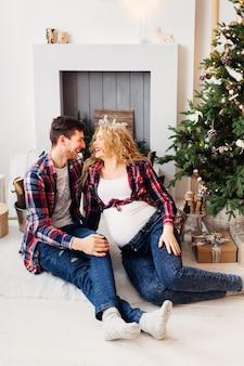 Młodzi ludzie wkrótce będą szczęśliwymi rodzicami na tle świątecznych ozdób