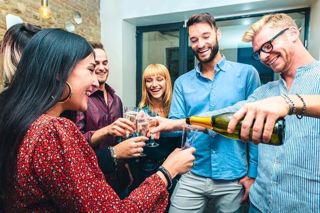 Młodzi ludzie wlewają szampana i świętują urodziny - grupa młodych współpracowników świętuje i wznosi toast za sukces - selektywna ostrość