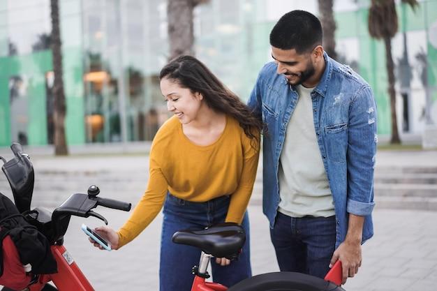 Młodzi ludzie wypożyczający rower elektryczny za pomocą aplikacji na smartfona