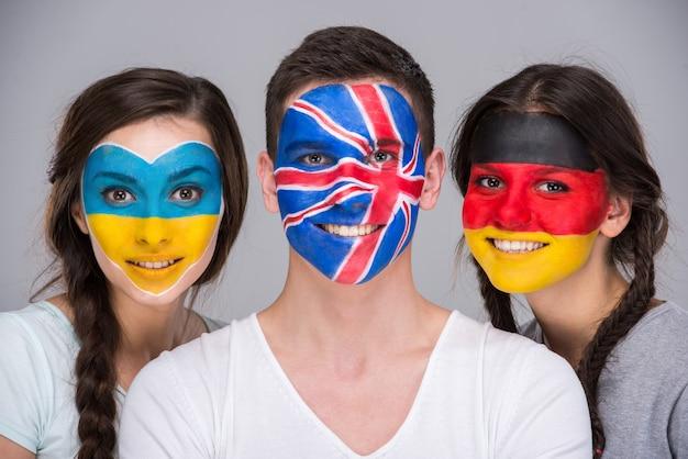 Młodzi ludzie z flagami narodowymi namalowanymi na twarzach.