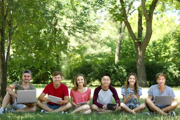 Młodzi ludzie z gadżetami w parku