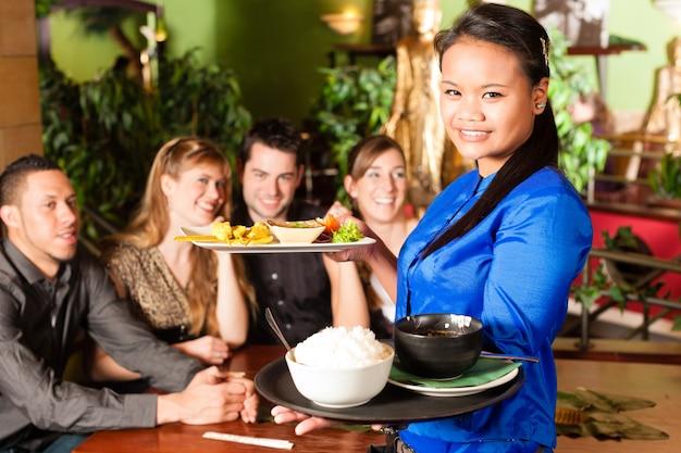 Młodzi ludzie z kelnerką je w tajlandzkiej restauraci