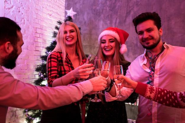 Młodzi ludzie z kieliszkami szampana na przyjęciu bożonarodzeniowym