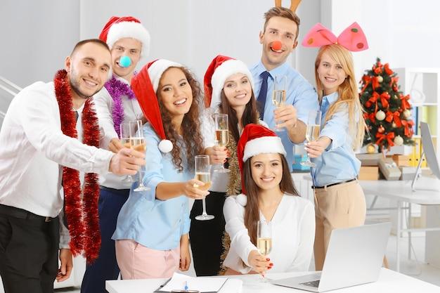 Młodzi ludzie z kieliszkami szampana obchodzi boże narodzenie na imprezie firmowej w biurze