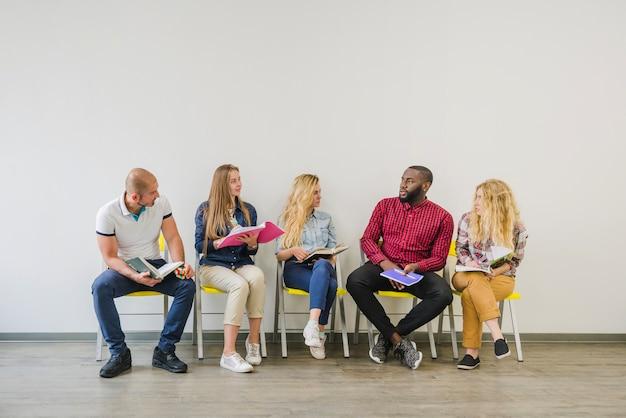 Młodzi ludzie z notatkami na krzesłach