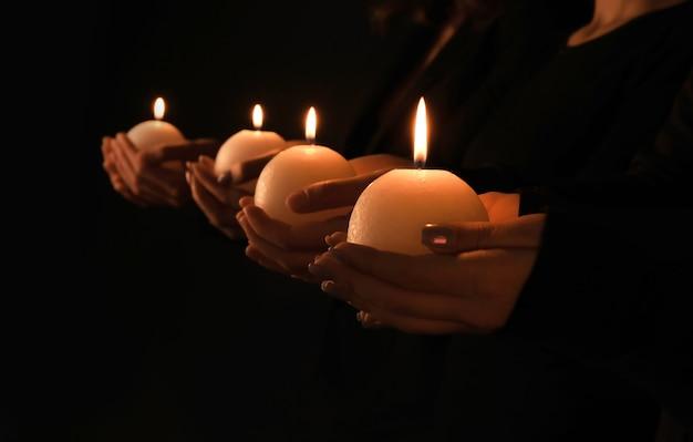 Młodzi ludzie z płonącymi świecami w ciemności