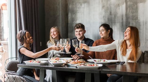 Młodzi ludzie zbierają się razem na obiad