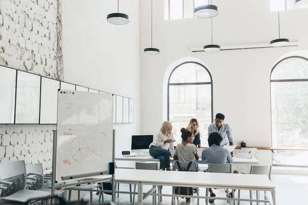 Młodzi menadżerowie i ceo spędzają rano czas w sali konferencyjnej. wewnętrzny portret zespołu marketerów omawiających nowe cele w dużym, nowoczesnym biurze.