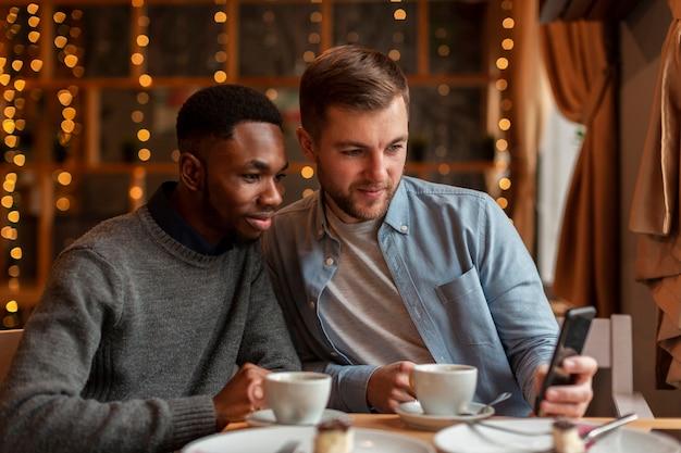 Młodzi męscy przyjaciele patrzeje na wiszącej ozdobie