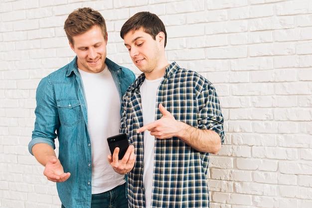 Młodzi męscy przyjaciele pokazuje coś na telefonie komórkowym jego przyjaciel