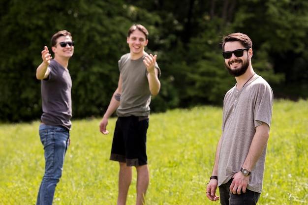 Młodzi mężczyźni dzwoniący przyjaciel na pikniku