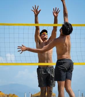 Młodzi mężczyźni grający w siatkówkę plażową na plaży w słoneczny dzień