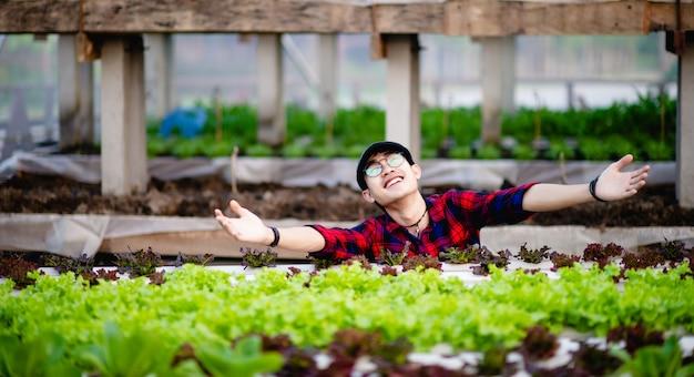 Młodzi mężczyźni i ekologiczne warzywa sałatkowe i jego szczęśliwy uśmiech