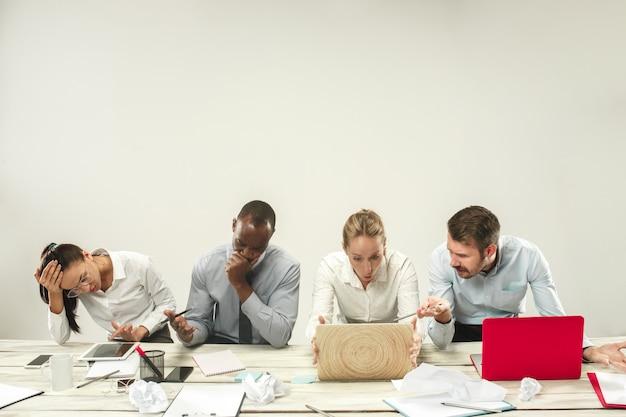 Młodzi mężczyźni i kobiety siedzą w biurze i pracują na laptopach. koncepcja emocji