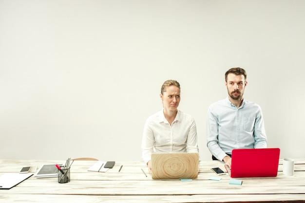 Młodzi mężczyźni i kobiety siedzą w biurze i pracują na laptopach.
