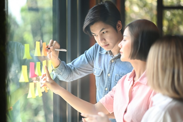Młodzi mężczyźni i kobiety w biurze pracują razem. używają długopisu i dłoni, aby wycelować notatkę w szybę.