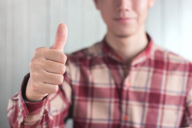 Młodzi mężczyźni noszą czerwony wzór scott koszula palec kciuk na białym drewnie