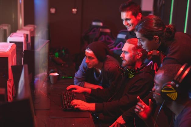Młodzi mężczyźni pomagający przyjacielowi przejść grę wideo