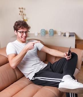 Młodzi mężczyźni przeprowadzają wideorozmowę telefonem, siedząc na beżowej sofie w domu