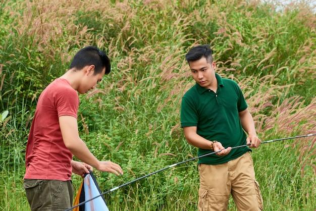 Młodzi mężczyźni rozbijający namiot