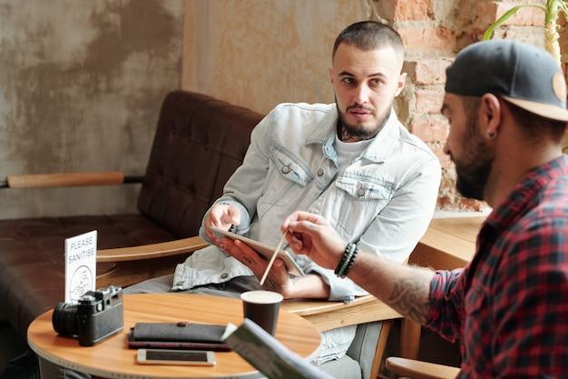 Młodzi mężczyźni siedzący w hotelowej kawiarni i pijący kawę, omawiając pomysły na sesję zdjęciową