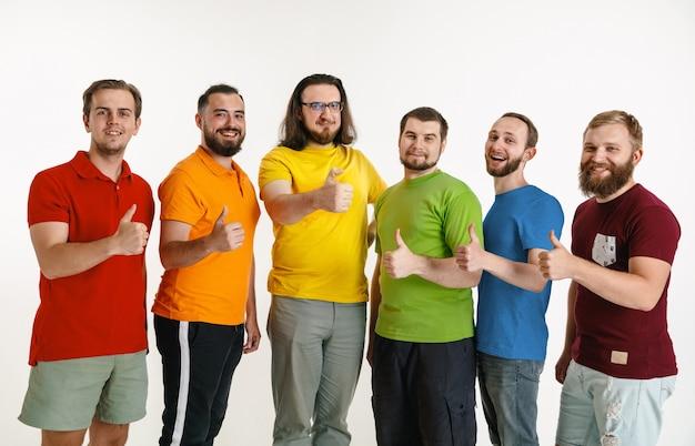 Młodzi mężczyźni ubrani w kolory flagi lgbt na białej ścianie. kaukascy mężczyźni w koszulach w kolorze czerwonym, pomarańczowym, żółtym, zielonym, niebieskim i fioletowym. duma lgbt, prawa człowieka i koncepcja wyboru.
