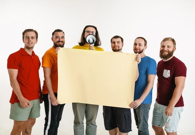 Młodzi mężczyźni ubrani w kolory flagi lgbt na białym tle na białej ścianie. kaukaskie modele męskie w koszulach w kolorze czerwonym, pomarańczowym, żółtym, zielonym, niebieskim i fioletowym. duma lgbt, prawa człowieka, koncepcja wyboru. miejsce.