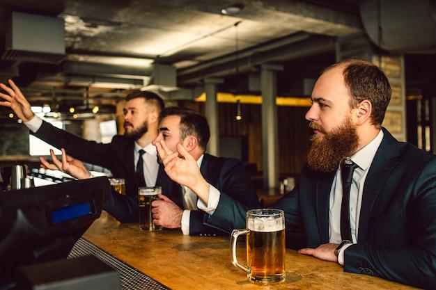 Młodzi mężczyźni w garniturach siedzą w barze i kibicują. oni oglądają telewizję. faceci są emocjonalni. machają i wyciągają ręce do przodu.