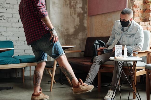Młodzi mężczyźni witają się gestem stopy podczas spotkania w kawiarni po kwarantannie koronawirusa