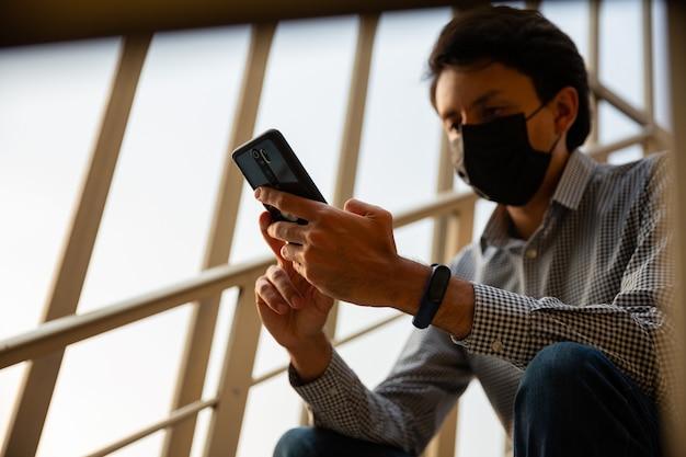 Młodzi mężczyźni z maską siedzi na schodach posiłku. trzyma telefon w rękach