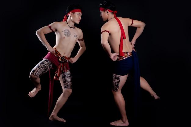 Młodzi mężczyźni z tajlandii wykonujący tradycyjny taniec