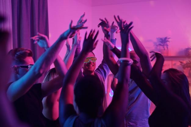 Młodzi międzykulturowi czarujący przyjaciele podnoszący ręce podczas wspólnego tańca na imprezie domowej w salonie oświetlonym różowym oświetleniem