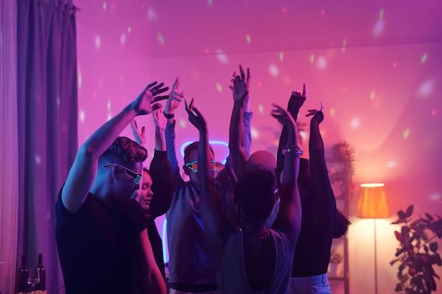 Młodzi międzykulturowi przyjaciele w eleganckich casualowych ubraniach podnoszący ręce podczas wspólnego tańca na imprezie domowej w salonie oświetlonym różowym oświetleniem