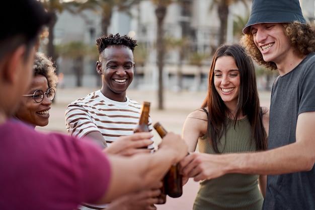 Młodzi międzyrasowi ludzie wznoszący tosty z piwem na zewnątrz