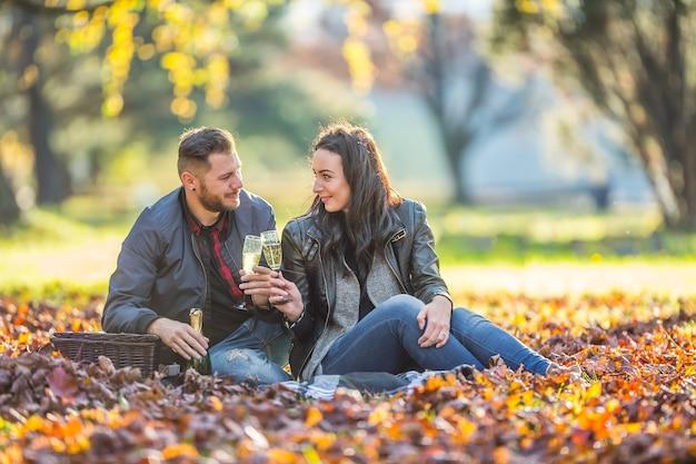 Młodzi miłośnicy szczęśliwej pary urządzają piknik w jesiennym parku szczęśliwa para z szampanem