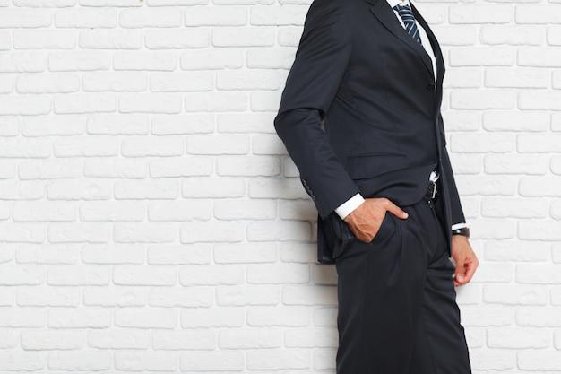 Młodzi modni mężczyzna w kostiumu przeciw ściana z cegieł