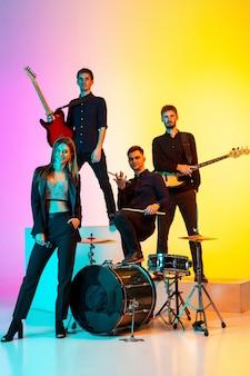 Młodzi muzycy kaukascy, zespół występujący w świetle neonowym na gradientowym tle studyjnym