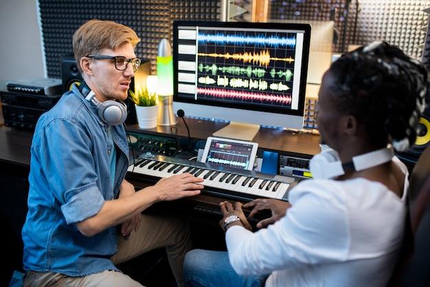 Młodzi muzycy wieloetniczni w codziennych ubraniach siedzą obok miejsca pracy w studiu nagrań i dyskutują o nowym systemie miksowania dźwięków