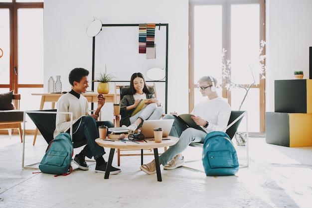 Młodzi nastolatkowie siedzi w fotelach w coworking