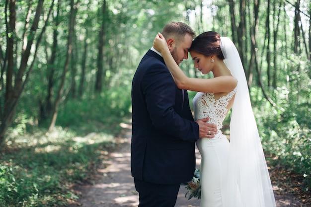 Młodzi nowożeńcy cieszą się romantycznymi chwilami na zewnątrz.