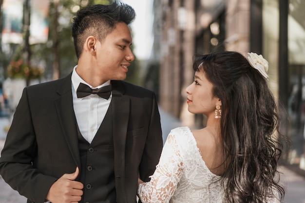 Młodzi nowożeńcy pozują razem na zewnątrz